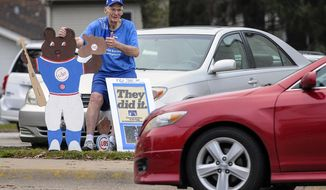 "Chicago Cubs fan Dan Wessel, 79, of Moline, Ill., gives a passing motorist the thumbs up Thursday morning, Nov. 3, 2016, after they honked their horn in celebration of the Cubs winning the World Series. Wessel said he brought his homemade Cubs signs out to the corner of 16th Street and 31st Ave., in Moline, because he wanted to savior the moment of the Cubs winning the world championship. ""It's a once in a lifetime thing,"" said the die-hard Cubs fan. (Todd Mizener/The Rock Island Argus via AP)"