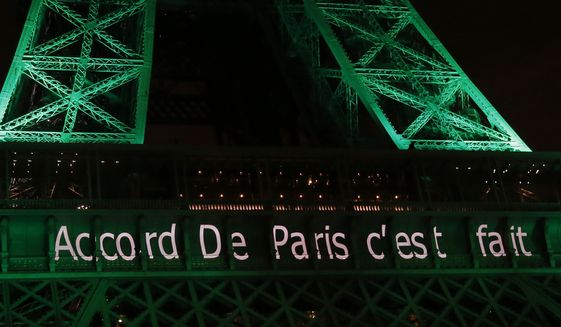 """The Eiffel Tower lit up in green to mark the success of the Paris Agreement, Friday Nov.4, 2016 in Paris. The Paris Agreement on climate change enters into force Friday faster than anyone had anticipated, after a year with remarkable success in international efforts to slash man-made emissions of carbon dioxide and other global warming gases. Inscription reads, """"Paris Agreement it's done"""".(AP Photo/Michel Euler)"""