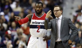 Washington Wizards guard John Wall (2) and Washington Wizards head coach Scott Brooks talk during the first half of an NBA basketball game against the Atlanta Hawks, Friday, Nov. 4, 2016, in Washington. (AP Photo/Alex Brandon)
