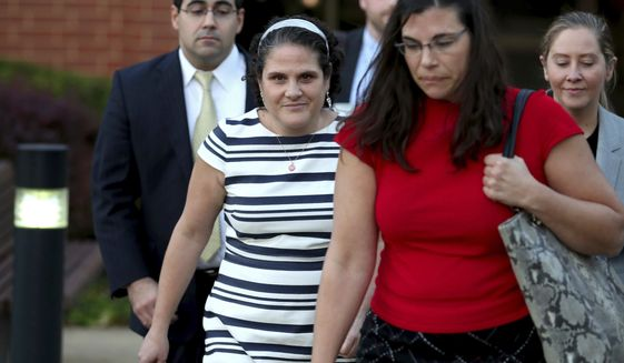 Nicole Eramo, center, leaves the federal courthouse, Wednesday, Oct. 19, 2016 in Charlottesville, Va.. Eramo, a University of Virginia administrator who sued Rolling Stone magazine over its portrayal of her in a now-discredited story about a gang rape said Wednesday that the magazine's apologies for its journalistic failures didn't go far enough. (Ryan M. Kelly/The Daily Progress via AP)