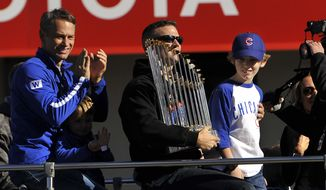 Chicago Cubs president of baseball operations Theo Epstein holds the Commissioner's Trophy while his son, Jack, right, and Chicago Cubs vice president of baseball operations and general manager Jed Hoyer, left, look on during a parade outside Wrigley Field honoring the World Series champions Friday, Nov. 4, 2016, in Chicago. (AP Photo/Paul Beaty)