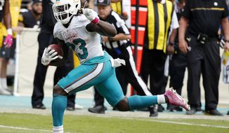 FILE - In this Oct. 16, 2016, file photo, Miami Dolphins running back Jay Ajayi (23) runs the ball during the second half of an NFL football game against the Pittsburgh Steelers, in Miami Gardens, Fla. Ajayi has a chance to become the first NFL player to rush for 200 yards in three consecutive games when the Dolphins play the Jets. (AP Photo/Wilfredo Lee, File)