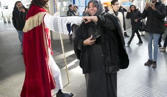 "Sinterklaas, traditionally played by a white person, dances with a Muslim woman at subway station in Amsterdam, Netherlands, Saturday, Nov. 5, 2016. The steam boat carrying Sinterklaas, the Dutch equivalent of Santa Claus is not due to chug into the historic harbor of Maassluis until next weekend, but the annual polarized debate about his helper ""Black Pete"" has been underway for weeks. (AP Photo/Peter Dejong)"