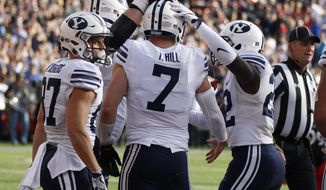 Brigham Young quarterback Taysom Hill (7) is congratulated by teammates after scoring a touchdown against Cincinnati during the first half of an NCAA college football game, Saturday, Nov. 5, 2016, in Cincinnati. (AP Photo/Gary Landers)