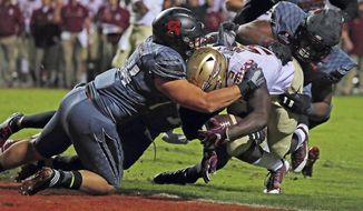 Florida State running back Jacques Patrick (9) drives into the end zone for a touchdown through the tackle of North Carolina State's Ford Howell (44) and Dravious Wright, right, during the first half of an NCAA college football game in Raleigh, N.C., Saturday, Nov. 5, 2016. (AP Photo/Karl B DeBlaker)