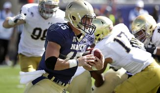 Navy quarterback Will Worth (15) runs past Notre Dame defensive lineman Andrew Trumbetti (98) and linebacker James Onwualu (17) for a 60-yard gain during the first half of an NCAA college football game Saturday, Nov. 5, 2016, in Jacksonville, Fla. (AP Photo/John Raoux)