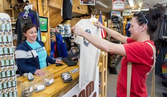ADVANCE FOR WEEKEND EDITIONS NOV. 5-6 -  In this Friday, Oct. 21, 2016, photograph, Sara Judge, left, manager of the Dam Store, located at the mouth of the Big Thompson Canyon, helps customer Jessica Wiechman, right, from West Point, Neb., with a purchase in Loveland, Colo. Wiechman, in town to see her brother, was brought to the store for the view of the canyon from its tower. Owners of shops such as the Dam Store are concerned about a drop off in sales as a nine-month project begins to repair Highway 34 from damages sustained during the flood of 2013. (Michael Brian/Loveland Reporter-Herald via AP)