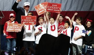 Republican presidential candidate Donald Trump poses with children on stage at a campaign rally in Sterling Heights, Mich., Sunday, Nov. 6, 2016. (AP Photo/Paul Sancya)