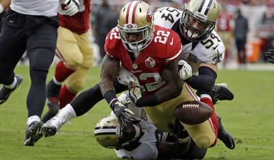 San Francisco 49ers running back Mike Davis (22) fumbles the ball near the goal line as New Orleans Saints inside linebacker Nate Stupar (54) and free safety Jairus Byrd, bottom, look on during the second half of an NFL football game Sunday, Nov. 6, 2016, in Santa Clara, Calif. (AP Photo/Tony Avelar)