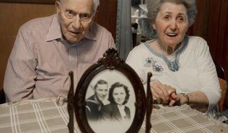 In this Oct. 21, 2016 photo, Philip and Dorothy Dougan pose as a photo sits on the table in front of them at their home in Madison County, Tenn. They are celebrating their 75th wedding anniversary. (Kenneth Cummings/The Jackson Sun via AP)