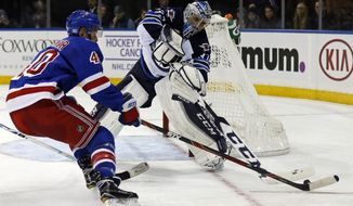 Winnipeg Jets goalie Michael Hutchinson (34) knocks the puck away from New York Rangers right wing Michael Grabner (40) in the second period of an NHL hockey game, Sunday, Nov. 6, 2016, in New York. (AP Photo/Adam Hunger)