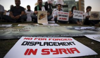 In this picture taken on Friday, Oct. 7, 2016, Syrian citizens attend a sit-in against the forced displacement in Syria, in front the United Nations headquarters, in downtown Beirut, Lebanon. Syrian opposition figures and refugees point to an array of obstacles facing the displaced who want to return home, saying that the government is machinating to discourage potentially restive populations from returning to areas they fled during the war. (AP Photo/Hussein Malla)
