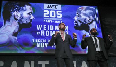 """FILE- In this Sept. 27, 2016 file photo, UFC middleweight fighters Chris Weidman, left, and Yoel Romero pose for photos during a news conference for UFC 205 in New York. Weidman and Romero are on the first major UFC card to be held in New York after the state legislature legalized the sport earlier in 2016. """"This is a dream come true,"""" says middleweight Chris Weidman, a native New Yorker, who will be part of the undercard for the Saturday, Nov 12, 2016, pay-per-view event that features a lightweight title bout between Conor McGregor and Eddie Alvarez. (AP Photo/Julie Jacobson, File)"""