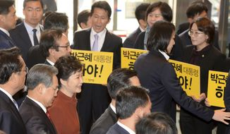 """South Korean President Park Geun-hye, third from left front, arrives as the opposition party's lawmakers holding signs reading """"President Park Geun-hye Step Down"""" upon her arrival to meets with National Assembly Speaker Chung Sye-kyun at the National Assembly in Seoul, South Korea, Tuesday, Nov. 8, 2016. South Korean prosecutors have raided the Seoul office of Samsung Electronics in connection with a snowballing influence-peddling scandal involving President Park Geun-hye's longtime confidante. (Bae Jae-man/Yonhap via AP)"""