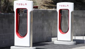 CORRECTS TO TESLA ENDING UNLIMITED FREE USE, NOT ALL FREE USE - FILE - This undated file photo shows Tesla Motors charging stations neat Truckee, Calif.  Electric car maker Tesla Motors says it will end unlimited free use of its worldwide charging station network. The company says cars ordered after Jan. 1, 2017 will get roughly 1,000 miles worth of credits at the supercharging stations. After credits are used, owners will have to pay fees. Cars ordered or sold on or before Jan. 1 would still get free charging.  (Margaret Moran/Sierra Sun via AP, File)