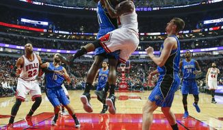 Chicago Bulls guard Jimmy Butler, right, goes to the basket against Orlando Magic center Bismack Biyombo, left, during the first half of an NBA basketball game, Monday, Nov. 7, 2016, in Chicago. (AP Photo/Kamil Krzaczynski)