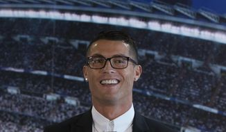 Real Madrid's Cristiano Ronaldo speaks after signing a new contract at the Santiago Bernabeu stadium in Madrid, Spain, Monday, Nov. 7, 2016. Real Madrid have extend Ronaldo's contract until June 2021, when the three-time world player of the year will be 36. Financial details were not released, although the star forward is expected to remain the team's top-paid player. (AP Photo/Paul White)