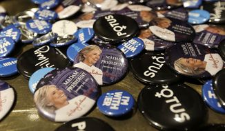 Buttons supporting presidential candidate Hillary Clinton fill a table for sale at an election night party for Democrats Tuesday, Nov. 8, 2016, in Seattle. (AP Photo/Elaine Thompson)