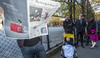 A voter, left, reads The New York Times, which features presidential candidates Donald Trump, left, and Hillary Clinton, right, as he waits to enter a polling station in the Brooklyn borough of New York, Tuesday, Nov. 8, 2016. (AP Photo/Alexander F. Yuan)