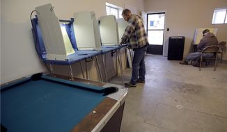 John Wilson, left, from Bear Creek, Mo., and Russell Madison, from Humansville, Mo., vote in a game room on a family farm Tuesday, Nov. 8, 2016 near Humansville, Mo. (AP Photo/Charlie Riedel)