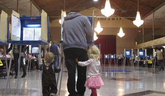 A voter fills out his ballot with his two small children on Election Day, Tuesday, Nov. 8, 2016, in Helena, Mont. (AP Photo/Matt Volz)