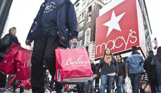 In this Friday, Nov. 27, 2015, file photo, shoppers carry bags as they cross a pedestrian walkway near Macy's in Herald Square, in New York. (AP Photo/Bebeto Matthews, File)