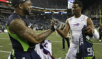 Seattle Seahawks defensive end Damontre Moore, left, trades jerseys with Buffalo Bills wide receiver Justin Hunter, right, after an NFL football game, Monday, Nov. 7, 2016, in Seattle. The Seahawks beat the Bills 31-25. (AP Photo/John Froschauer)