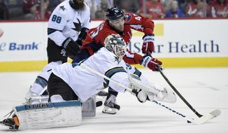 San Jose Sharks goalie Martin Jones, front, reaches for the puck against Washington Capitals right wing Tom Wilson, top, during the first period of an NHL hockey game, Tuesday, Nov. 8, 2016, in Washington. (AP Photo/Nick Wass)