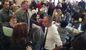 Mayor Jorge Elorza, foreground, speaks to voters at the Summit Commons polling place Tuesday morning, Nov. 8, 2016 in Providence, R.I., where some voters waited more than an hour to cast ballots. Elorza came to explain how poll workers were trying to speed up the process and to thank voters for their patience. (AP Photo/Matt O'Brien)