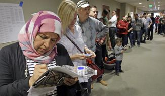 Hana Alshamry, left, waits in line with others to vote at the Holladay City Hall Tuesday, Nov. 8, 2016, in Holladay, Utah. Utah's mostly Mormon, mostly Republican voters are going to the polls Tuesday to determine if the GOP's five-decade winning streak in presidential elections will remain intact or be snapped. (AP Photo/Rick Bowmer)