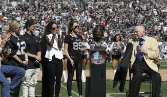 Former Oakland Raiders head coach John Madden, right, unveils a Pro Football Hall of Fame bust for former quarterback Ken Stabler next to Stabler's family at a ceremony during halftime of an NFL football game between the Oakland Raiders and the Atlanta Falcons in Oakland, Calif., Sunday, Sept. 18, 2016. (AP Photo/Marcio Jose Sanchez) **FILE**