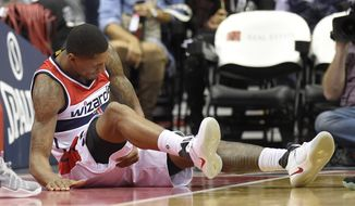 Washington Wizards guard Bradley Beal grabs his leg after he was injured during the second half of the team's NBA basketball game against the Boston Celtics, Wednesday, Nov. 9, 2016, in Washington. Beal did not return. The Wizards won 118-93. (AP Photo/Nick Wass)