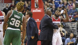 Washington Wizards guard John Wall, right, gestures toward Boston Celtics guard Marcus Smart (36) during the second half of an NBA basketball game, Wednesday, Nov. 9, 2016, in Washington. Wall was charged with a flagrant type-2 foul against Smart and was ejected. The Wizards won 118-93. (AP Photo/Nick Wass)