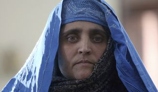 "National Geographic's famed green-eyed ""Afghan Girl"" Sharbat Gulla poses for a photo during a meeting with Afghan President Ashraf Ghani, at the Presidential palace in Kabul, Afghanistan, Nov. 9, 2016. Afghanistan's president on Wednesday welcomed home Gulla who was deported from Pakistan after a court had convicted her on charges of carrying a forged Pakistani ID card and staying in the country illegally. (AP Photo/Rahmat Gul)"