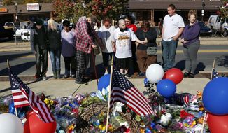 A group prays in front of a makeshift memorial for the Canonsburg Police officers who were shot when they responded to a domestic call early Thursday, Nov 10, 2016, in Canonsburg, Pa. A gunman with a history of domestic abuse shot at police officers before he and a woman were found dead following a reported fight at their apartment, authorities said. (AP Photo/Gene J. Puskar)