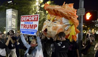 Protesters carry a paper head of President-elect Donald Trump during a protest in front of City Hall Wednesday, Nov. 9, 2016 in Los Angeles. A day after  Trump's election as president, the divisions he exposed only showed signs of widening as many thousands of protesters flooded streets across the country to condemn him.  (Keith Birmingham/The Pasadena Star-News/SCNG via AP)