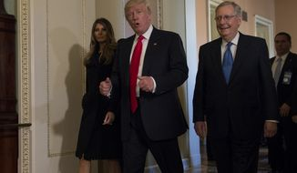 President-elect Donald Trump, accompanied by his wife Melania, and Senate Majority Leader Mitch McConnell of Ky., gestures while walking on Capitol Hill in Washington, Thursday, Nov. 10, 2016, after meeting.  (AP Photo/Molly Riley)