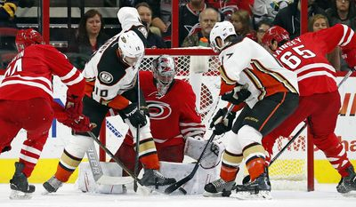 Anaheim Ducks' Corey Perry (10) and Ryan Kesler (17) battle for the puck in front of Carolina Hurricanes goalie Cam Ward (30) with Hurricanes' Jaccob Slavin (74) and Ron Hainsey (65) providing support during the second period of an NHL hockey game, Thursday, Nov. 10, 2016, in Raleigh, N.C. (AP Photo/Karl B DeBlaker)
