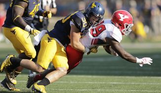 FILE - In this Sept. 10, 2016, file photo, West Virginia linebacker Justin Arndt (30) tackles Youngstown State running back Martin Ruiz (29) during an NCAA college football game in Morgantown, W.Va.  West Virginia travels to Texas on Saturday where it will try to slow down Longhorns running back D'Onta Foreman, who ran for 341 yards against Texas Tech last week (AP Photo/Raymond Thompson, File)