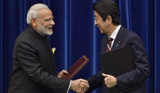 India's Prime Minister Narendra Modi, left, and Japan's Prime Minister Shinzo Abe shake hands after signing a joint statement at Abe's official residence in Tokyo, Japan, Friday, Nov. 11, 2016. After their bilateral meeting, both countries signed a civilian nuclear cooperation agreement that will allow Japan to export nuclear plant technology to India. (Franck Robichon/Pool Photo via AP)