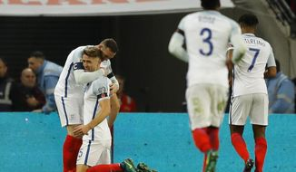 England's Gary Cahill, second left is congratulated by teammate England's Wayne Rooney, right, after he scored his sides third goal of the game during the World Cup 2018 Group F qualification soccer match between England and Scotland at Wembley stadium in London, Friday, Nov. 11, 2016. (AP Photo/Frank Augstein)