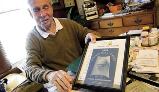 ADVANCE FOR USE SATURDAY, NOV. 12, 2016 AND THEREAFTER - In this  May 3, 2016 photo, Walt Fields, 91, shows off the program from the night his college basketball team was inducted into the Indiana Hall of Fame during an interview at his home in Fulton, Ill. He served in the Pacific with the Navy during WWII, then joined the Brooklyn Dodgers' farm system. As a teacher, a coach, and an MLB scout, sports has been a consistent thread through his life. (Alex T. Paschal/Sauk Valley Media via AP)
