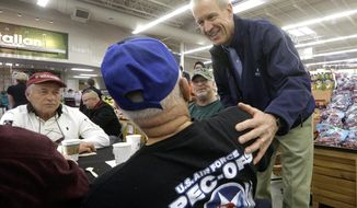 """Illinois Gov. Bruce Rauner, right, greets veterans while participating in """"Breakfast to Veterans for Veterans Day"""" Friday, Nov. 11, 2016, in Springfield, Ill. (AP Photo/Seth Perlman)"""