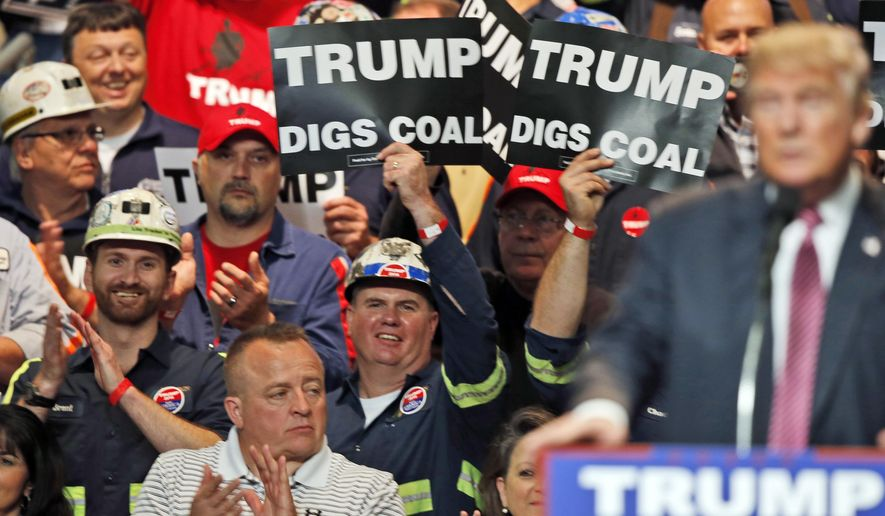 Coal miners wave signs as Donald Trump speaks during a rally in Charleston, W.Va., on May 5. (Associated Press) **FILE**