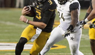 Missouri quarterback Drew Lock, left, runs past Vanderbilt's Dare Odeyingbo, right, during the third quarter of an NCAA college football game Saturday, Nov. 12, 2016, in Columbia, Mo. (AP Photo/L.G. Patterson)