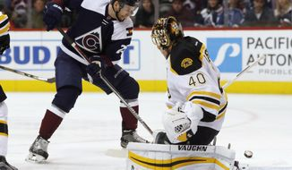 Boston Bruins goalie Tuukka Rask, right, of Finland, deflects a shot off the stick of Colorado Avalanche center Mikhail Grigorenko, of Russia, in the first period of an NHL hockey game Sunday, Nov. 13, 2016, in Denver. (AP Photo/David Zalubowski)