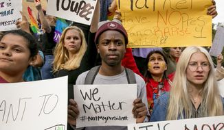 FILE - In this Thursday Nov. 10, 2016 file photo, from left, Celeste Ramirez, 20, Erin Ckodre , 21, Ronald Elliott, 18, Patricia Romo, 22, and Rose Ammons, 18, hold up signs during a rally at Texas State University in San Marcos, Texas, to protest Donald Trump's presidential election victory. For the combatants in America's long-running culture wars, the triumph of Trump and congressional Republicans was stunning _ sparking elation on one side, deep dismay on the other. (Jay Janner/Austin American-Statesman via AP)