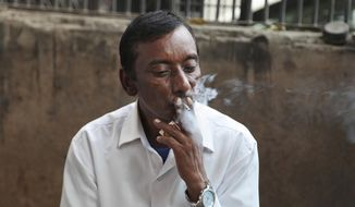 FILE- In this Nov. 3, 2016 file photo, an Indian man smokes a cigarette in New Delhi, India. A global conference on tobacco control has pledged to hold the tobacco industry legally liable for health consequences of smoking and protect public health policies from the influence of tobacco companies.Representatives from around 180 countries participating in the World Health Organization's global tobacco control treaty negotiations on Saturday adopted a declaration in which they also vowed to prohibit or regulate the sale of e-cigarettes. (AP Photo/Altaf Qadri, File)