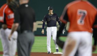 Japan's Shohei Otani stands at second base after hitting a ground-rule double as Netherlands players talk to an umpire in the seventh inning of their international exhibition series baseball game at Tokyo Dome in Tokyo, Sunday, Nov. 13, 2016. (AP Photo/Shizuo Kambayashi)