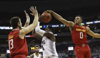Georgetown's L.J. Peak (0) guarded by Maryland' Ivan Bender (13), is blocked from behind by Maryland's Anthony Cowan (0) as he attempts to shoot during the second half of an NCAA college basketball game in Washington, Tuesday, Nov. 15, 2016. Maryland won 76-75. (AP Photo/Manuel Balce Ceneta)